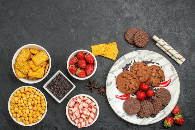 Вид сверху вкусного шоколадного печенья с разными закусками на темном столе сладкого чая с печеньем