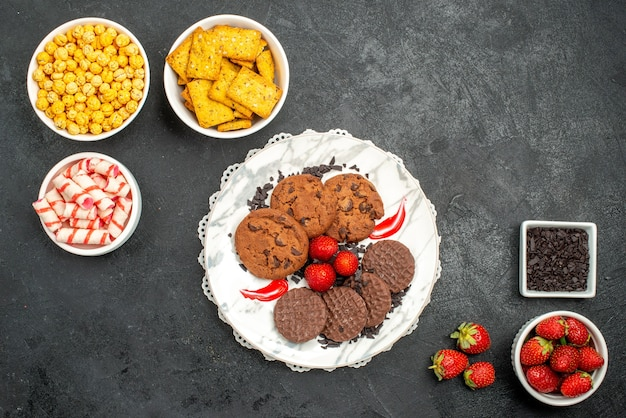 トップビューダークデスクティースウィートクッキーにさまざまなスナックが入ったおいしいチョコビスケット