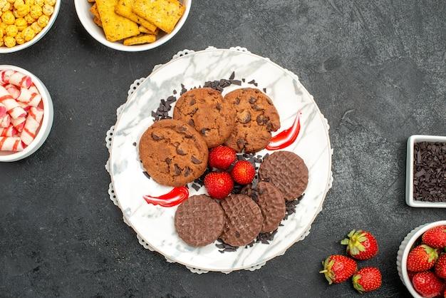 Вкусное шоколадное печенье с разными закусками на темном полу, сладкое печенье, вид сверху