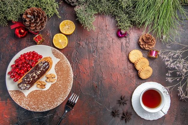 暗いテーブルの上のベリーとお茶とおいしいチョコエクレアの上面図甘いケーキパイデザート