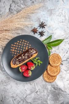 Vista dall'alto squisiti bignè al cioccolato con biscotti su torta di biscotti da dessert con biscotto leggero