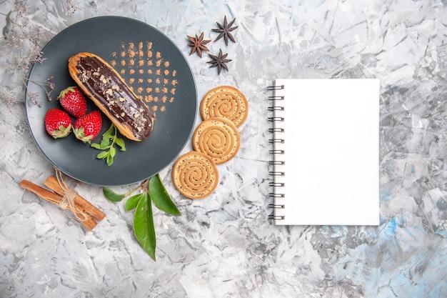 Вид сверху вкусные шоколадные эклеры с печеньем на светлом столе, бисквитный торт, десертное печенье