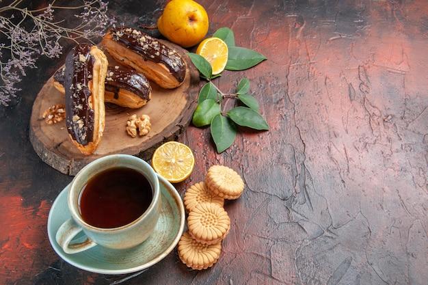 Вид сверху вкусные шоколадные эклеры с чашкой чая на темном столе, десерт, сладкий торт