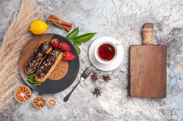 Вид сверху вкусные шоколадные эклеры с чашкой чая на белом печенье, торт, десерт, бисквит