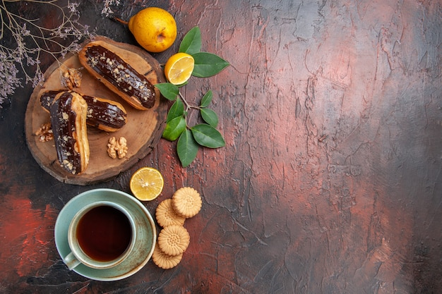 Top view yummy choco eclairs with cup of tea on dark table dessert sweet cake