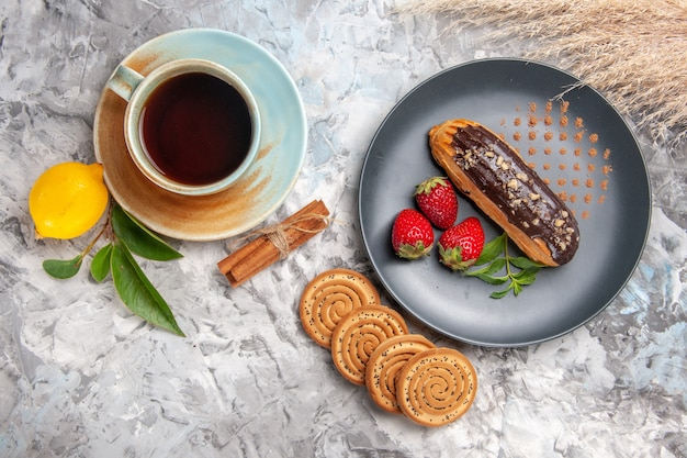 Top view yummy choco eclairs with cup of tea on light biscuit cookies dessert