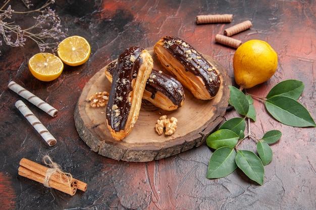 暗いテーブルの上の果物とおいしいチョコエクレアの上面図ケーキデザート甘い