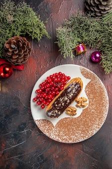 Vista dall'alto yummy choco eclairs con bacche rosse sul dolce da dessert torta torta tavolo scuro
