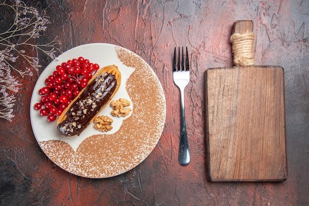 어두운 테이블 케이크 파이 디저트 달콤한에 빨간 열매와 상위 뷰 맛있는 초코 eclairs