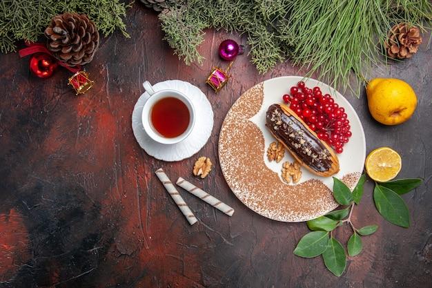 暗いテーブルの上の赤いベリーとおいしいチョコエクレアの上面図パイケーキデザート甘い