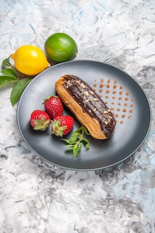 Vista dall'alto deliziosi bignè al cioccolato con fragole su caramelle da dessert con torta leggera da scrivania
