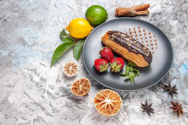 Вкусные шоколадные эклеры с клубникой на легком десертном бисквите, вид сверху