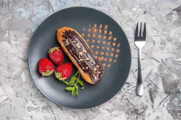 Вкусные шоколадные эклеры с клубникой на легком торте, десертные конфеты, вид сверху