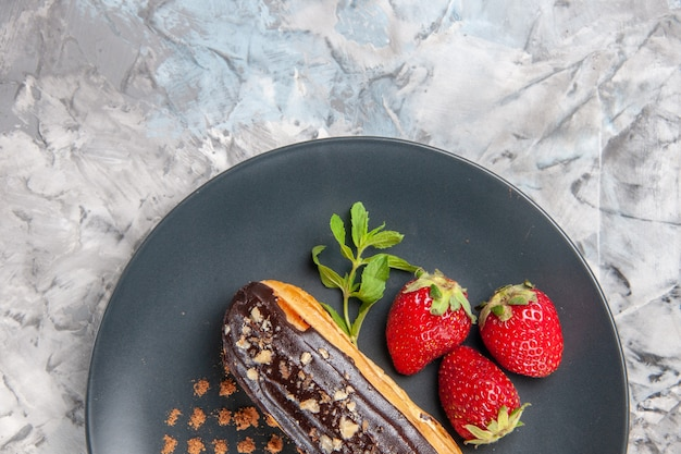 Вкусные шоколадные эклеры с клубникой на легких десертных конфетах, вид сверху