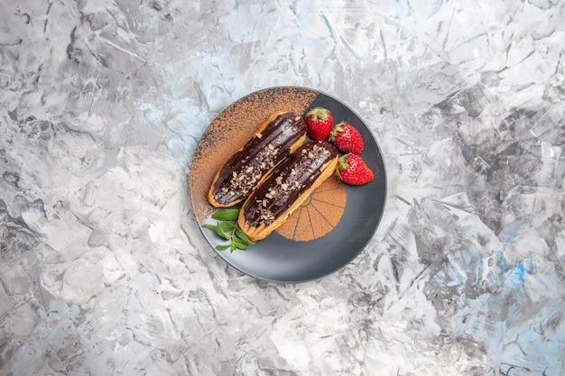 Вкусные шоколадные эклеры с клубникой на легком десертном бисквитном печенье, вид сверху
