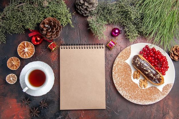 暗い床のパイの甘いデザートケーキにお茶とベリーとおいしいチョコエクレアの上面図