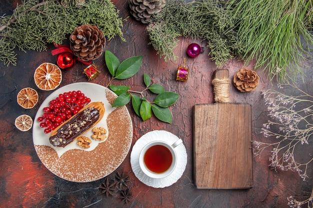暗いテーブルのパイの甘いケーキのデザートにお茶とベリーとおいしいチョコエクレアの上面図