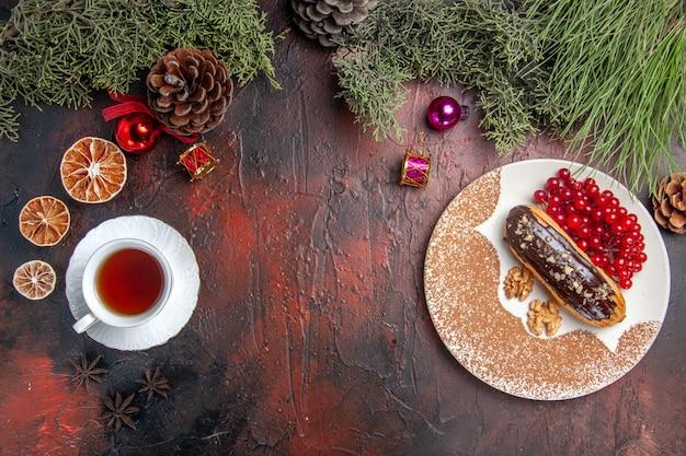 ダークテーブルパイの甘いデザートケーキにお茶とベリーを添えたトップビューのおいしいチョコエクレア