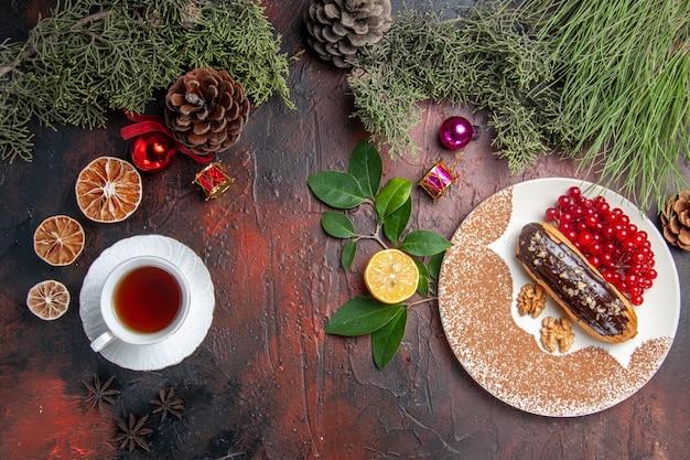 Вид сверху вкусные шоколадные эклеры с чаем и ягодами на темном столовом пироге, сладком десертном пироге