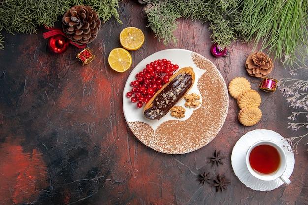 暗いテーブルの上のお茶とベリーとおいしいチョコエクレアの上面図甘いケーキパイデザート