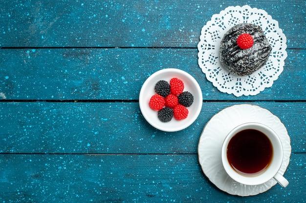 Vista dall'alto gustosa palla di cioccolato con una tazza di tè sul biscotto biscotto torta di tè scrivania rustica blu dolce