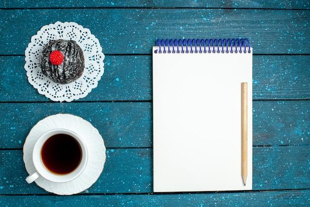Vista dall'alto gustosa palla di cioccolato con una tazza di tè sul biscotto biscotto torta dolce blu tè scrivania rustico