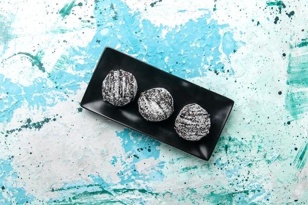 Vista dall'alto deliziose palline di cioccolato torte al cioccolato con glassa sulla superficie azzurra