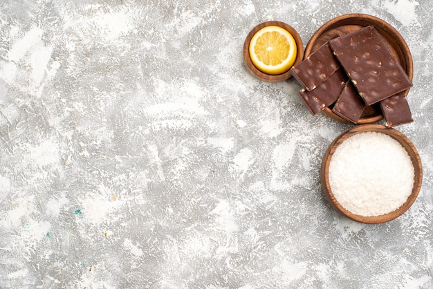 Top view of yummy chocolate bars with lemon slice on white surface