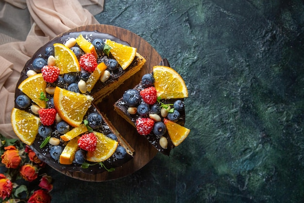 Top view yummy chocolate cake with fruits on dark