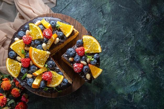 Torta al cioccolato gustosa vista dall'alto con frutta su fondo scuro