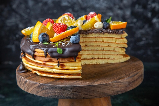 暗い上に果物と上面図おいしいチョコレートケーキ