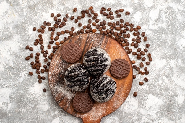 Top view of yummy chocolate cakes with cookies and brown coffee seeds on white surface
