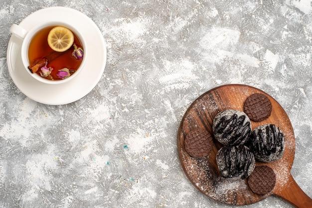 Vista dall'alto di deliziose torte al cioccolato con biscotti e tazza di tè sulla superficie bianca