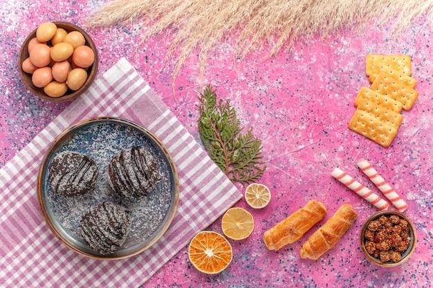 ピンクのクラッカーとキャンディーとトップビューおいしいチョコレートケーキ 無料写真