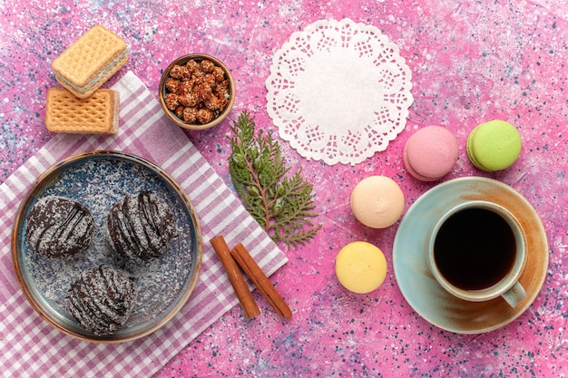 Вид сверху вкусные шоколадные торты с чашкой чая и макаронами на розовом