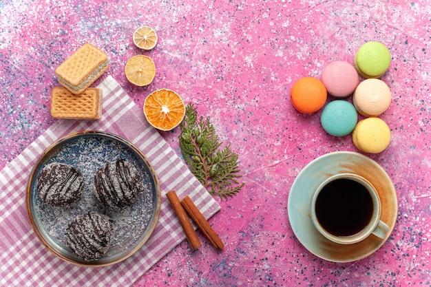 Vista dall'alto gustose torte al cioccolato con una tazza di tè e macarons francesi sul rosa