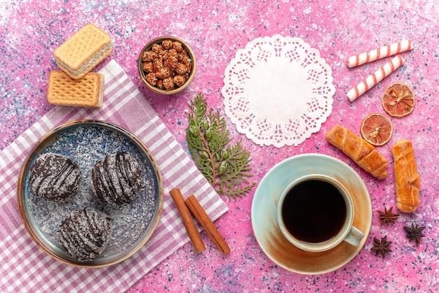 Vista dall'alto gustose torte al cioccolato con una tazza di tè su rosa chiaro