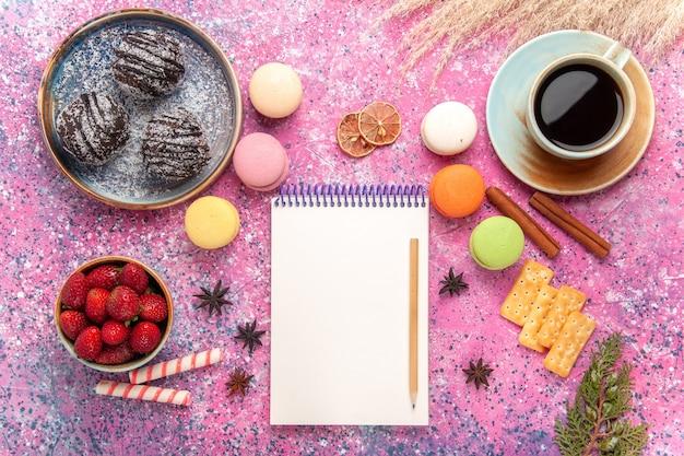 Vista dall'alto gustose torte al cioccolato con macarons francesi sul rosa