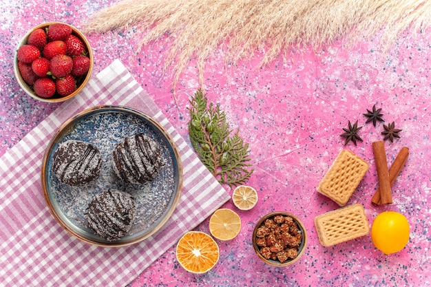 Vista dall'alto gustose torte al cioccolato con fragole rosse fresche sul rosa