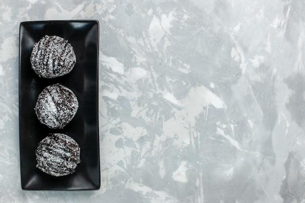 ライトホワイトの表面にアイシングが付いた上面図のおいしいチョコレートケーキ