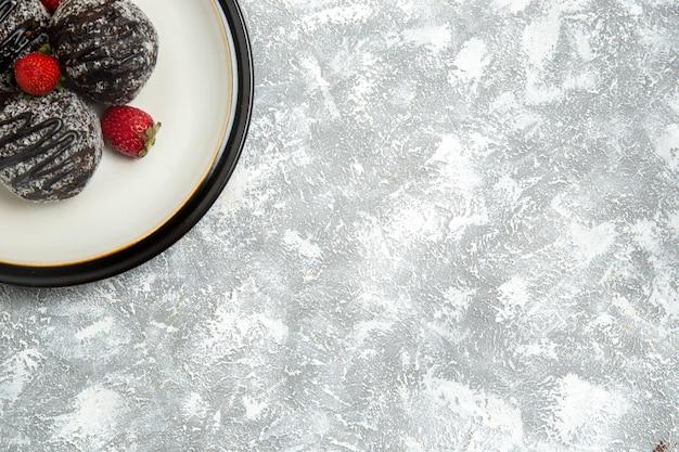 하얀 표면에 빨간 딸기가 있는 맛있는 초콜릿 케이크