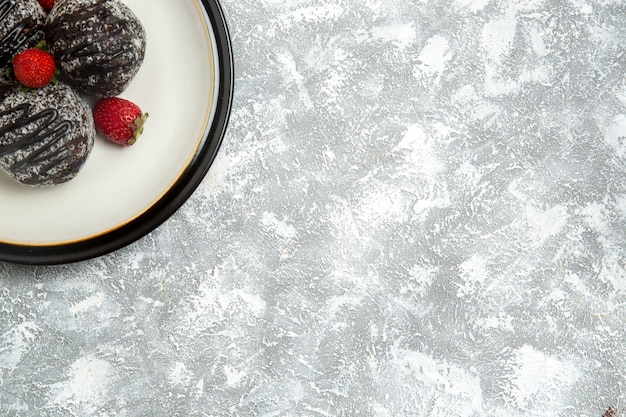 Vista dall'alto deliziose torte al cioccolato con fragole rosse su superficie bianca