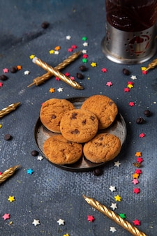 Vista dall'alto gustosi biscotti al cioccolato all'interno del piatto con piccoli segni zodiacali colorati e candele sul tè dolce dello zucchero del biscotto della scrivania scura