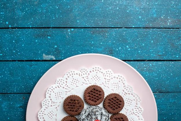 Vista dall'alto gustosi biscotti al cioccolato con torta al cioccolato su fondo rustico blu torta cacao tè biscotto dolce biscotto