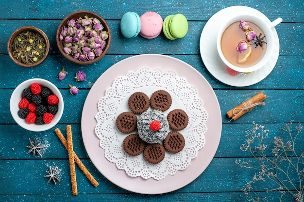上面図青い素朴なデスクケーキココアティー甘いビスケットクッキーにコンフィチュールとお茶とおいしいチョコレートクッキー