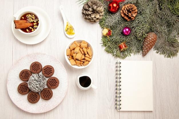 白い机の上に小さなココアケーキとお茶とトップビューおいしいチョコレートクッキー