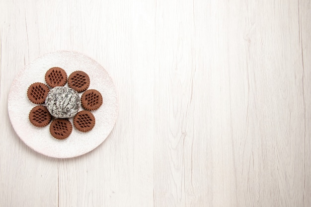 Вид сверху вкусного шоколадного печенья с маленьким какао-пирогом на белом