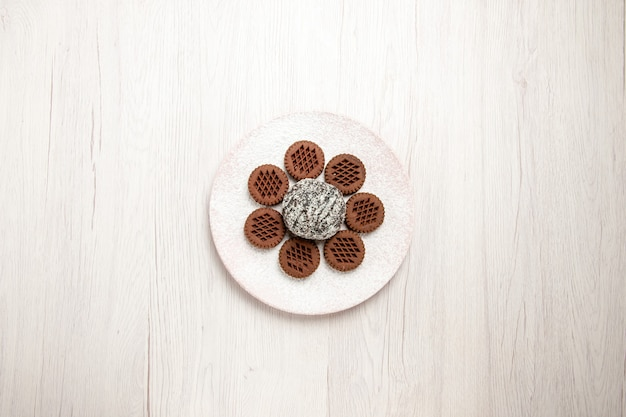 Top view yummy chocolate cookies with little cocoa cake on a white desk