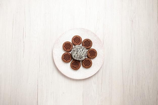 Vista dall'alto gustosi biscotti al cioccolato con piccola torta al cacao su una scrivania bianca