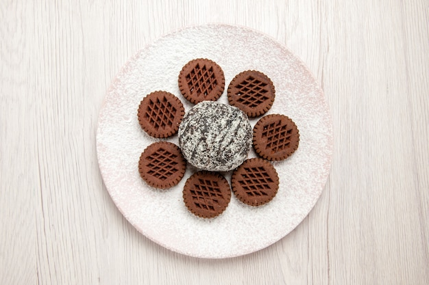 Vista dall'alto gustosi biscotti al cioccolato con piccola torta al cacao su bianco